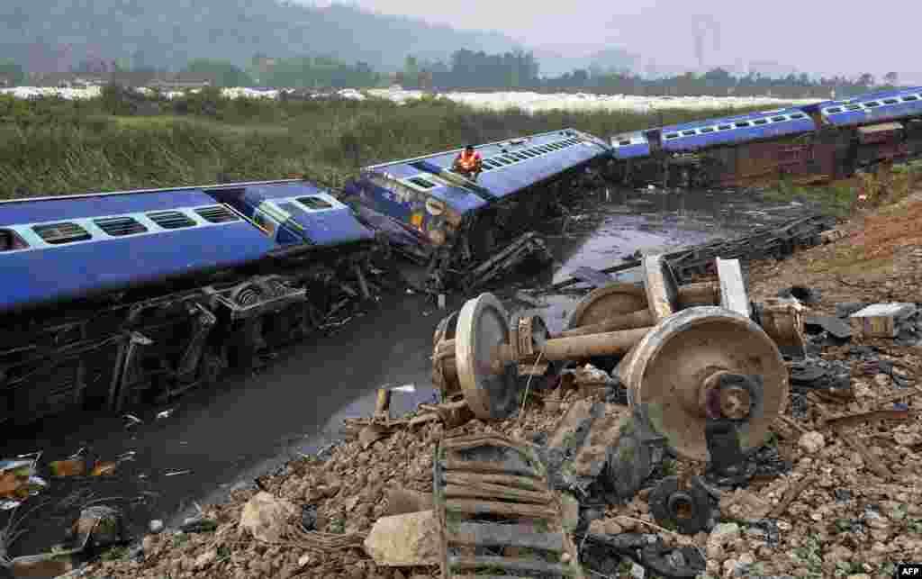 Một người cứu hộ trèo vào trong khoang tàu tìm kiếm hành khách bị mắc kẹt tại hiện trường nơi đoàn tàu bị trật bánh tại làng Teghria gần Trạm Xe lửa Jagiroad ở huyện Morigaon, cách thành phố Guwahati khoảng 90 km, ở bang Assam thuộc vùng đông bắc Ấn Độ.