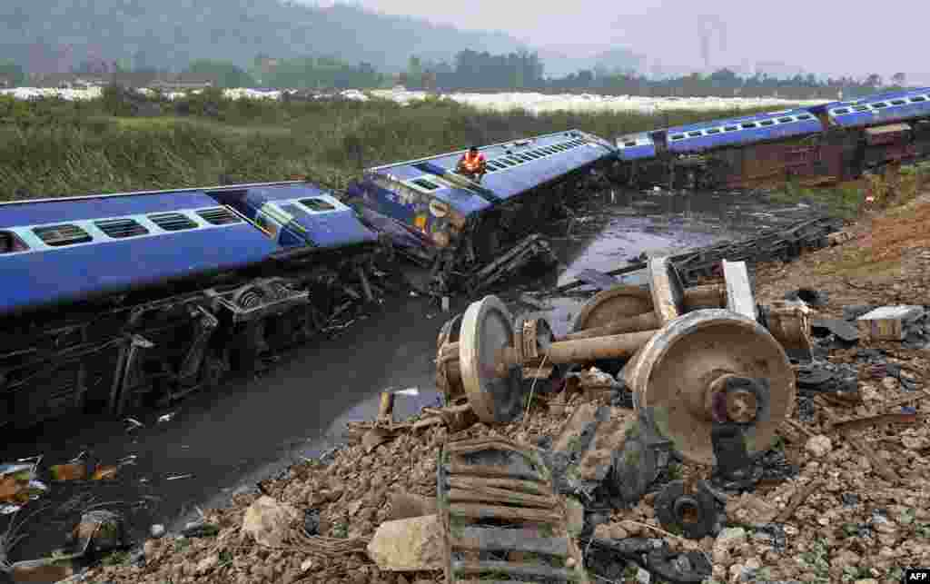 A rescuer climbs into a compartment in search of trapped passengers at the scene of a derailed train at Teghria village near Jagiroad Rail Station in Morigaon district, some 90 kms from Guwahati, in India's northeastern state of Assam.