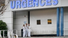 Medics are seen outside the emergency services at the CHU Nord Hospital in Grenoble, French Alps, where retired Formula 1 racer Michael Schumacher was taken following a skiing accident, Dec. 29, 2013.
