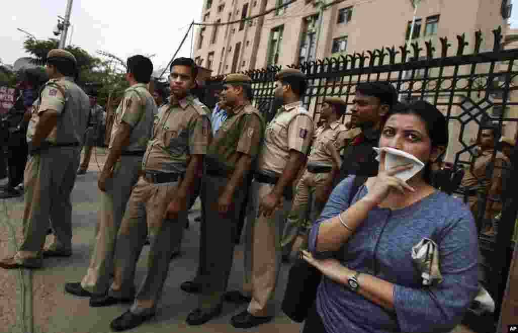 Delhi police secure a gate after protesters broke through a police barrier and entered the court complex demanding the death penalty for the four men convicted in the fatal gang rape of a young woman, New Delhi, Sept. 11, 2013.