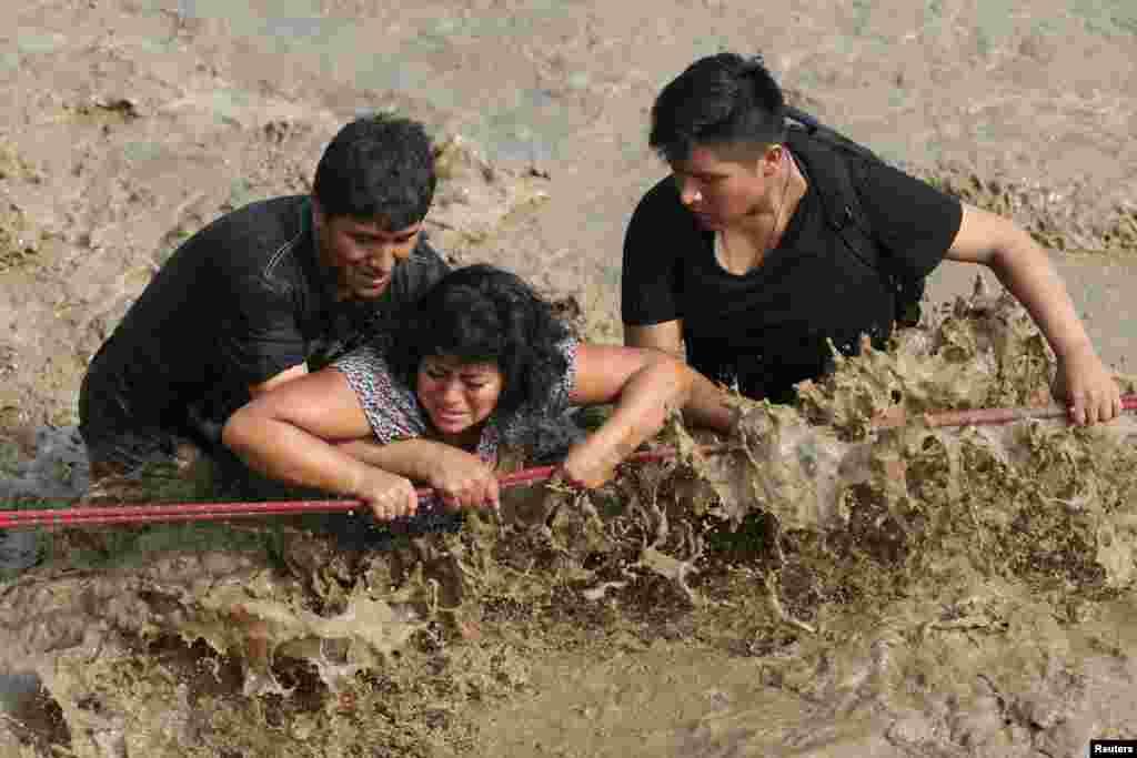 امدادی کارکن سیلاب سے متاثرہ ایک عورت کو محفوظ مقام پر منتقل کرنے کی کوشش کر رہے ہیں۔