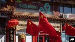 Un trabajador embozado con una mascarilla permanece junto a un local frente al que ondean varias banderas china, el pasado 3 de marzo.