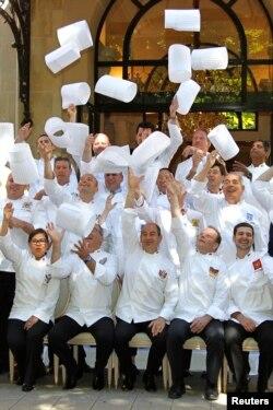 Anggota Club des Chefs des Chefs (Club of Leaders' Chefs) melemparkan topi koki mereka saat berpose di depan Plaza Athenee Hotel sebelum dimulainya pertemuan di Paris, Perancis, 23 Juli 2012. (REUTERS/Charles Platiau)