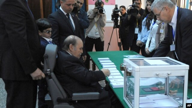 President Abdelaziz Bouteflika, sitting on a wheelchair, prepares to vote in the presidential elections in Algiers, Thursday, April 17, 2014.