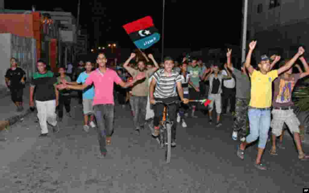 2011年8月22日清晨,民众在的黎波里近郊的塔朱拉欢庆反政府武装控制的黎波里大部分地区,包括具有象征意义的绿场,并逮捕了卡扎菲的儿子赛义夫。(AFP)