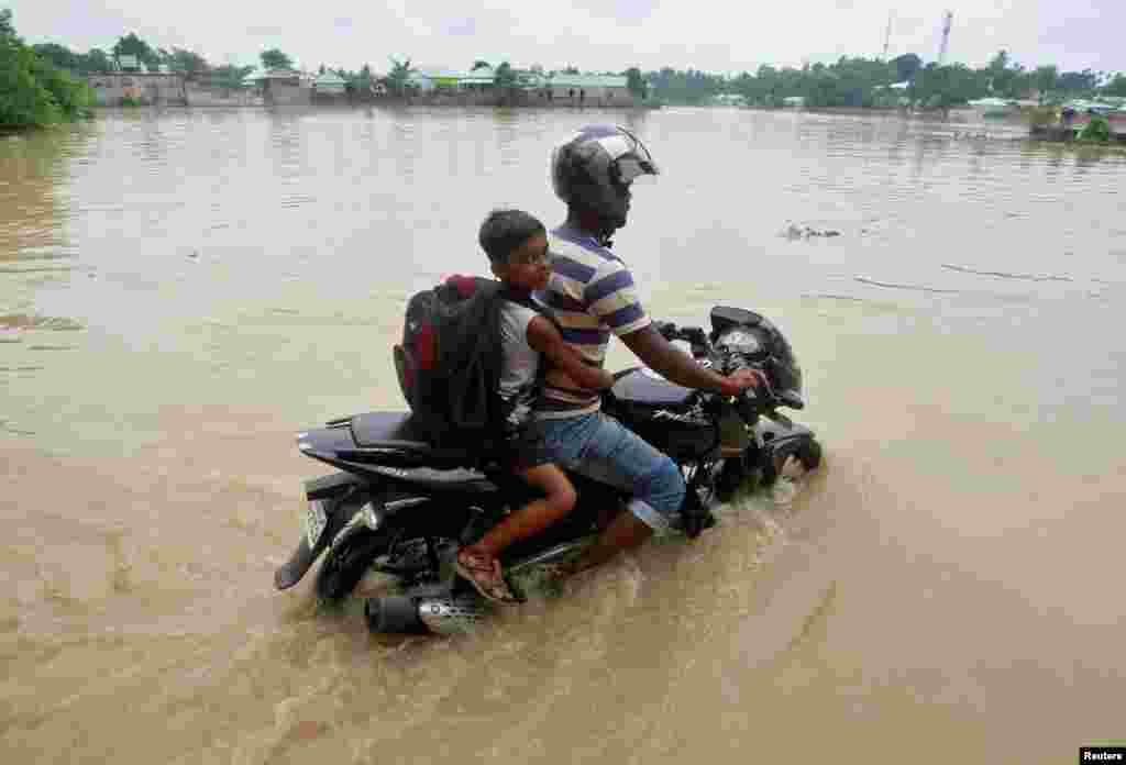 Seorang pria menaiki sepeda motor melewati jalan yang tergenang banjir di Agartala, India.