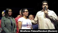 Venezuela's President Nicolas Maduro (R) speaks during an event with supporters, next to newly elected mayor of Libertador district Erika Farias (C) and President of Venezuela's National Constituent Assembly Delcy Rodriguez (L), in Caracas, Venezuela, Dec