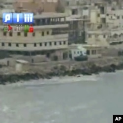 In this image taken from video made available Sunday Aug. 14, 2011, by Shaam News Network, in which they purport to show armored vehicles as they take up positions along the water front of Latakia, Syria.