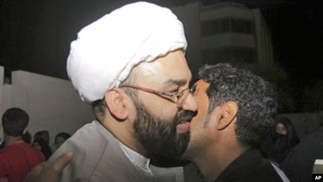 Sheik al-Nouri, in white turban, a Bahraini Shi'ite Muslim cleric who was standing trial for plotting against the regime, is kissed by a wellwisher outside the main police station in Manama, Bahrain, on being released before dawn, February 23, 2011