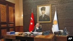 Turkey's Prime Minister Tayyip Erdogan, with a portrait of modern Turkey's founder Ataturk in the background, watches TV at his office at the AK Party headquarters in Ankara, Turkey, June 13, 2011