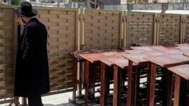 An ultra-Orthodox Jewish man speaks to a woman across a fence separating men and women at the Western Wall, the holiest site where Jews can pray in Jerusalem's old city, April 10, 2013.