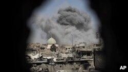 Una bomba explota detrás de la mezquita de al-Nuri en una foto captada a travez del orificio en una casa en Mosul.