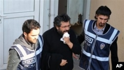 Police officers escort journalist Soner Yalcin, center, during a medical check in Istanbul, Turkey (File Photo - February 17, 2011)