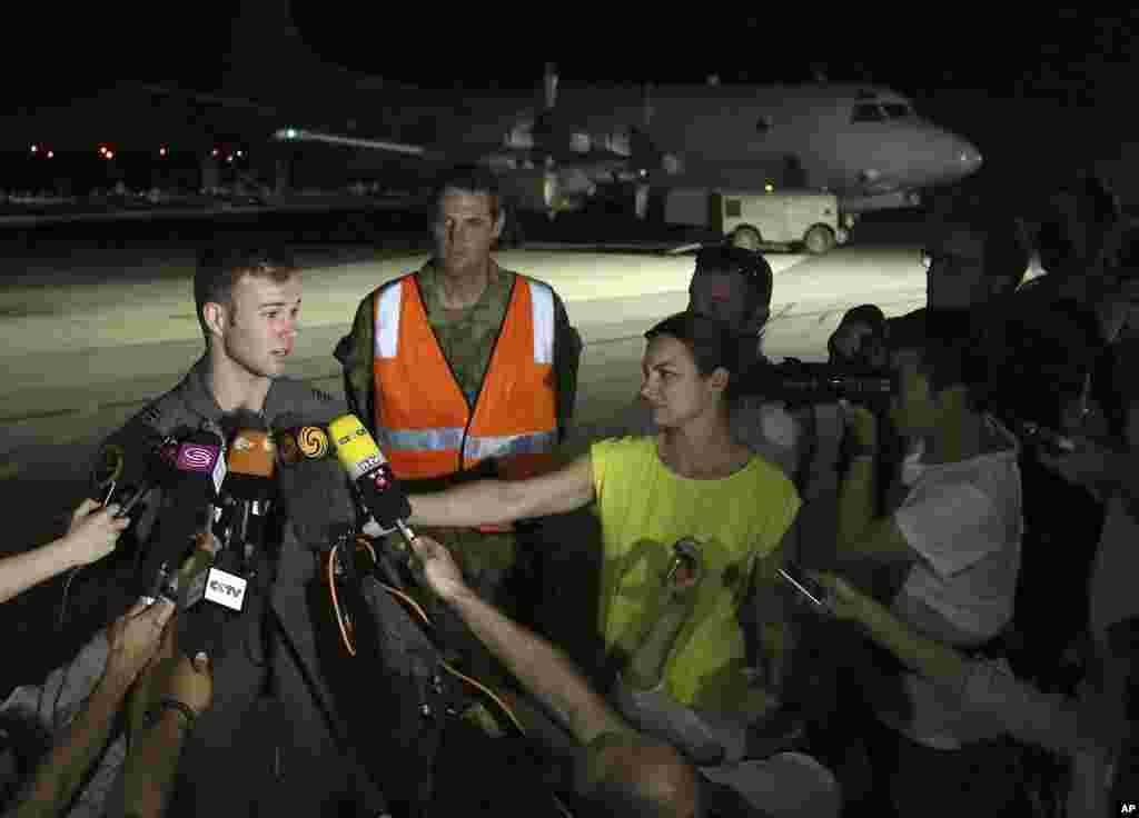 Royal Australian Air Force pilot Capt. Russell Adams, left, speaks to the media after returning from a search mission in an AP-3C Orion at Pearce Base, Perth, Australia, March 23, 2014.