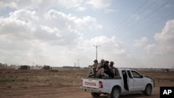 FILE - In this June 10, 2015 photo, Palestinian Hamas gunmen ride on the back of a pick-up truck as they patrol the border with Israel near the southern Gaza Strip town of Khan Younis.