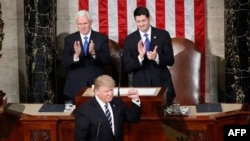 President Donald Trump, flanked by Vice President Mike Pence and House Speaker Paul Ryan of Wis., gestures on Capitol Hill in Washington, Feb. 28, 2017, before his address to a joint session of Congress.
