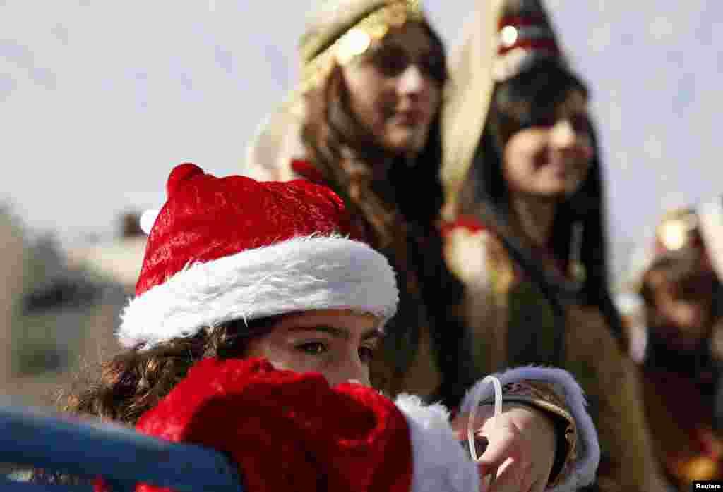 Seorang gadis kecil dari Palestina menonton parade Natal di luar Gereja Nativity di Bethlehem, Tepi Barat (24/12).ke