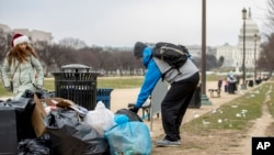 The Capitol building is visible as a man who declined to give his name picks up garbage and stacks it near a trash can during a partial government shutdown on the National Mall in Washington, Dec. 25, 2018.