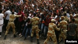 FILE - Security forces work to contain demonstrators at an anti-government rally in Bishoftu town, Oromia region, Ethiopia, Oct. 2, 2016. Initially triggered by land issues, the protests have shifted to include human rights and political power.