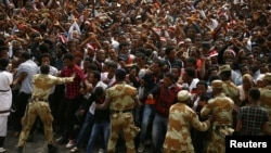 FILE -- Demonstrators chant slogans and flash the Oromo protest gesture during Irreecha, the thanksgiving festival of the Oromo people, in Bishoftu town, Oromia region, Ethiopia, Oct. 2, 2016.