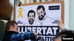 Activists put up banners with the photos of jailed leaders of Catalan pro-independence movements ANC (Catalan National Assembly) and Omnium Cutural, Jordi Sanchez and Jordi Cuixart, before Catalonia's former leader Carles Puigdemont addresses a news conference in Berlin, Germany, April 7, 2018.