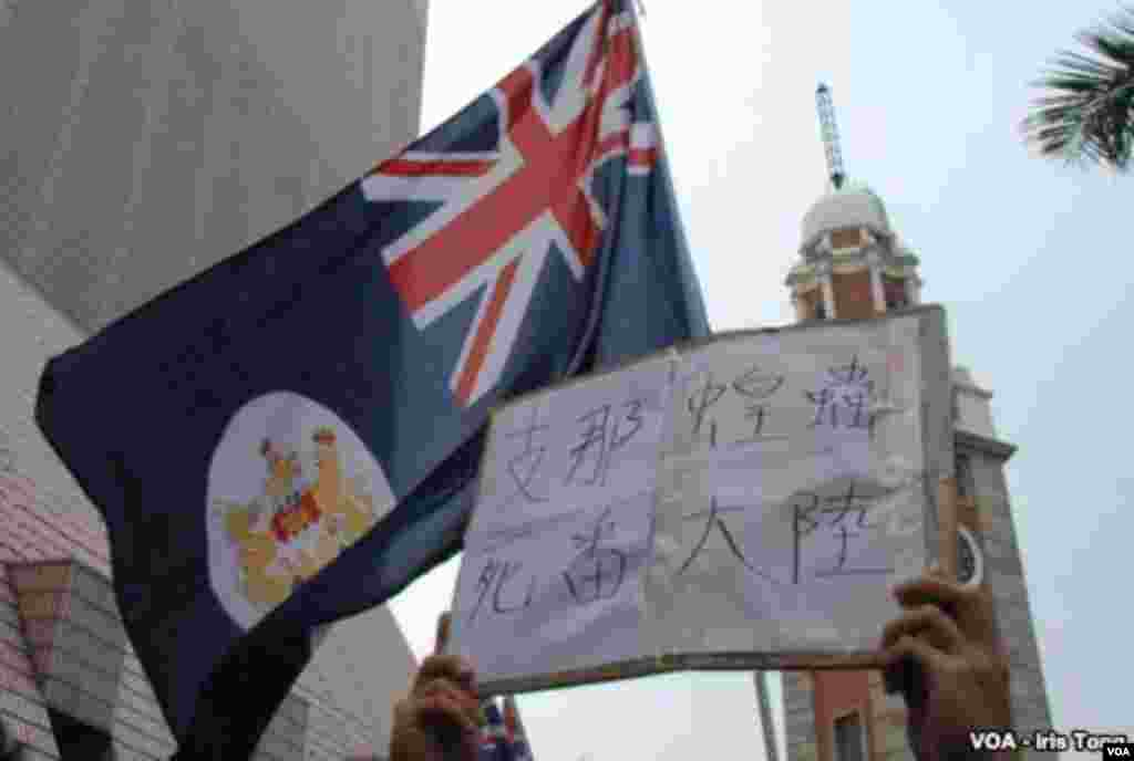 A banner held by a protester reads, 'China locusts, go back to the mainland.' Above, Hong Kong's former British colonial flag is raised by another protester in a gesture of defiance toward the Chinese government. (Iris Tong, VOA)