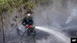 Seorang tentara menyemprotkan air untuk memadamkan api di Indralaya, Sumatra Selatan (16/9).