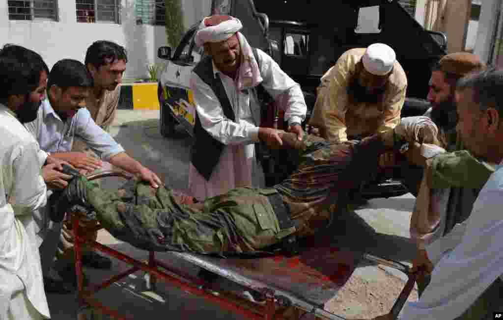 People carry a wounded security officer to a hospital in Quetta, Pakistan,  August 8, 2013.