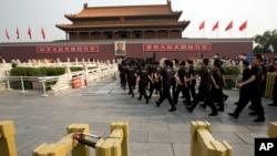 Petugas keamanan berbaris menuju jembatan di depan pintu gerbang Tiananmen, Beijing, China (31/5). Seorang pria menabrakkan mobil SUV dan membakarnya, setelah mengemudikannya melalui kerumunan turis yang ramai di tempat tersebut, tahun lalu. Dua wisatawan, pengemudi beserta istri dan ibu mertuanya dilaporkan tewas dalam insiden tersebut.