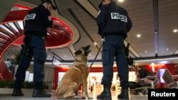 Polisi dengan anjing pelacak berjaga-jaga di dalam terminal 1 bandar udara Charles de Gaulle di Paris (19/5). (Reuters/Christian Hartmann)