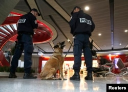 A police canine patrol stand guard inside terminal 1 at Charles de Gaulle airport in Paris, France, May 19, 2016.