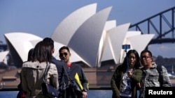 FILE - Chinese tourists taking pictures of themselves in front of the Sydney Opera House in Sydney, Australia.