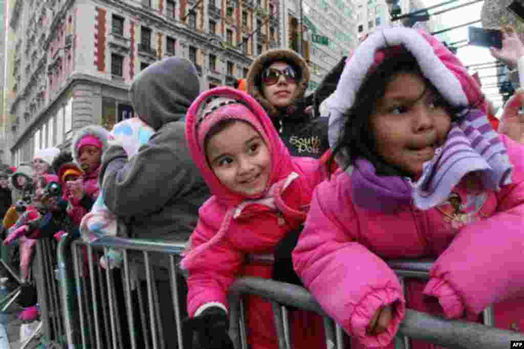 Gaila Reyes, 5, right, and her sister Michele Reyes, 4, second from right, react as they and others watch the 85th Annual Macy's Thanksgiving Day Parade as it moves across New York's 42nd Street Thursday Nov. 24, 2011. (AP Photo/Tina Fineberg)