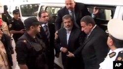 이집트 무함마드 무르시 전 대통령이 3일 재판장으로 들어서고 있다. 이집트 내무부 제공 동영상.