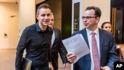 FILE - Max Schrems (L) and his lawyer, Herwig Hofmann, are seen walking in a hallway of the European Court of Justice in Luxembourg on Oct. 6, 2015.