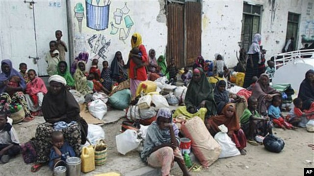 Families from the south of the country wait at the side of a street before making their way to a refugee camp seeking food and shelter, in Mogadishu, Somalia, August 3, 2011