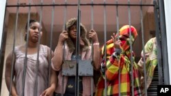People stand behind a gate at the entrance of an abandoned residential apartment building in the middle class Flamengo neighborhood of Rio de Janeiro, April 7, 2015.