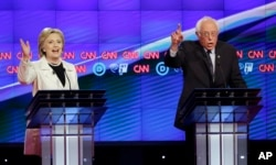 Democratic presidential candidates Sen. Bernie Sanders, I-Vt., right, and Hillary Clinton speak during the CNN Democratic Presidential Primary Debate at the Brooklyn Navy Yard, April 14, 2016.