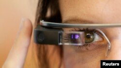 FILE - A woman wears Google glasses after a media presentation of a Google apartment in Prague, May 15, 2014.