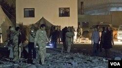 Pasukan pro-Gaddafi memeriksa lokasi serangan udara NATO di Tripoli yang menewaskan seorang putera Gaddafi (30/4).