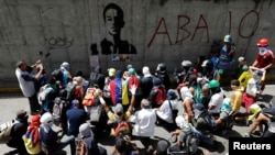 Opposition supporters sit next to a graffiti of 17-year-old protester Neomar Lander, who died during clashes with security forces, as they attend a rally against Venezuelan President Nicolas Maduro's government in Caracas, Venezuela, June 9, 2017.