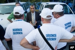 FILE - The head of the OSCE (Organization for Security and Cooperation in Europe) mission, acting Chief Observer Paul Picard, center, speaks to the other members in Rostov-on-Don, Russia, July 29, 2014. OSCE observers will be participating in the U.S. election.