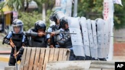 A Nicaraguan police officer aims his weapon at protesting students during a third day of violent clashes in Managua, Nicaragua, April 20, 2018. The Organization of American States have expressed concern over the heavy-handed crackdown, while also calling