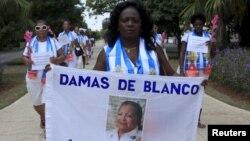 """Berta Soler, líder das """"Damas de Branco"""" grupo da oposição exibe estandartecm imagem da fundadora Laura Pollan, durante o protesto anti-governo semanal em Havana, (13 Setembro 2015, arquivo)"""