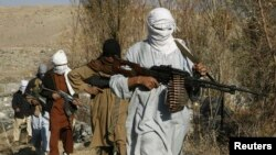 FILE - Taliban fighters carry weapons in an undisclosed location in Nangarhar province.