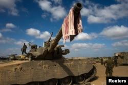 Mwanajeshi wa Israel asimama juu ya kifaru nje ya Ukanda wa Gaza, Julai 26, 2014.