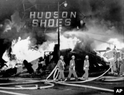 FILE - In this Aug. 14, 1965 file photo, firefighters battle a blaze set in a shoe store that collapses in flames during rioting in the Watts district of Los Angeles.