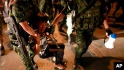 Des soldats interpellant des manifestants à Bangkok