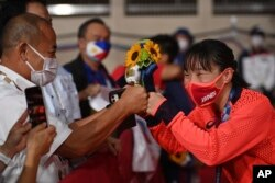 Petinju putri dari Jepang Sena Irie (kanan) menerima ucapan selamat seusai menerima medali emas dalam pertandingan final tinju kelas bulu 60 kg putri di Olimpiade Tokyo 2020, melawan petinju Filipina Nesthy Petecio, Selasa, 3 Agustus 2021, di Tokyo, Jepang. (AP)