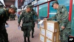 Los soldados del ejército de Ecuador comprueban las cajas electorales antes de distribuirlas en los colegios electorales de Quito, Ecuador, el sábado 1 de abril de 2017.
